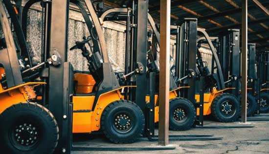 image - Three orange fork lifts parked in a row