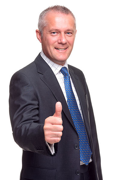 image of Man in Black suit smiling and holding right hand thumbs ups