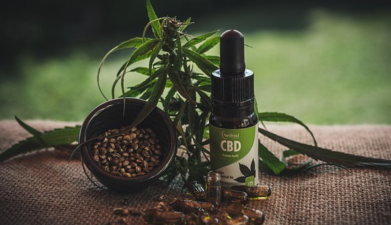 image of CBD oil in dropper bottle next to marijuana leaves