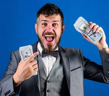 Happy businessman holding money from merchant cash advance loan