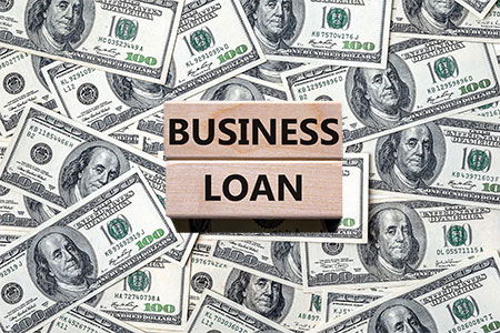 One hundred dollar bills with sign on top with words Business Loan