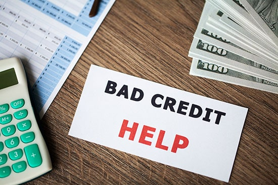Bad Credit Help Written On White Card On Desktop Next To Hundred Dollar Bills