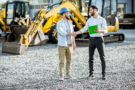 Two men shaking hands in front of typical yellow heavy construction equipment