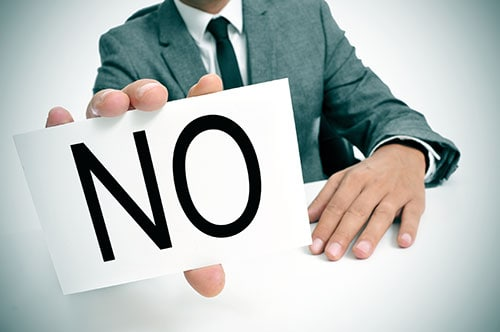 Man in business suit holding sign that says NO.