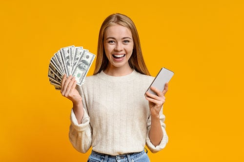 Millennial girl holding cash from alternative funding loan