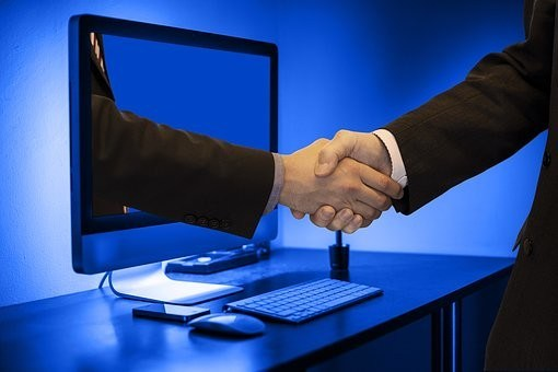 image- graphic of computer screen with hand extended out shaking businessman hand