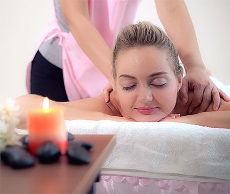 Health spa lady gettin massage in zen-like environment with candle burning and smooth rocks on table