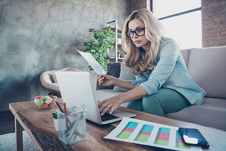 Lady working at home-based business with laptop on coffee table