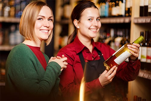 image- 2 ladies in liquor store holding liquor bottle