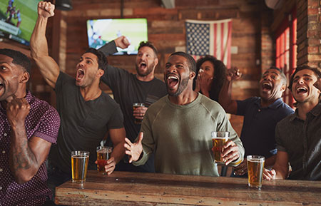 Group of male friends celebrating at a newly opened sports bar
