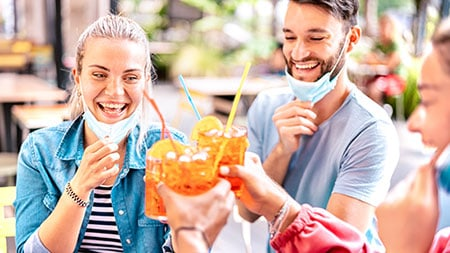 Friends drinking at reopened cocktail bar with face masks down