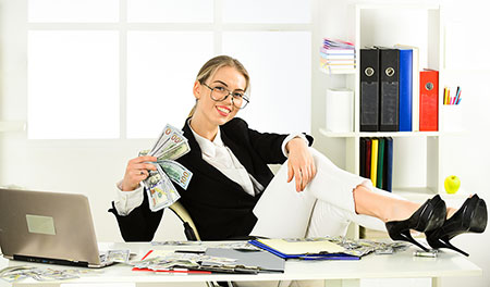 Woman behind desk with feet on desk and cash in hand celebrating receiving alternative financing business loan